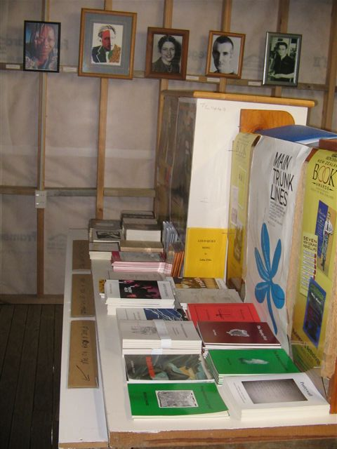 Some of the books and posters on display inside PANZA. In the background is the 'wall of fame', featuring photos of well-known New Zealand poets.